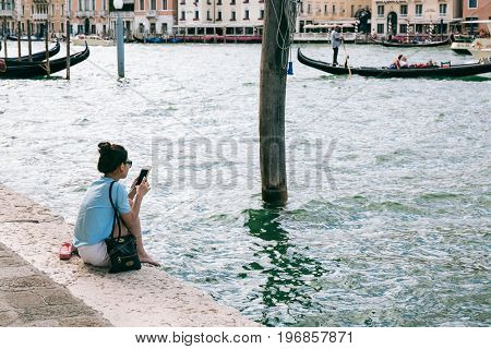VENICE, ITALY - JULY 02, 2017: Young woman sits on the bank of Grand Canal browsing mobile phone. The canal is the major water-traffic corridor in the city.