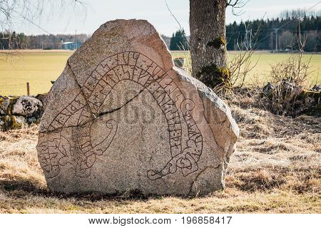 Old cracked rune stone from Sweden with red runes in the shape of a snake