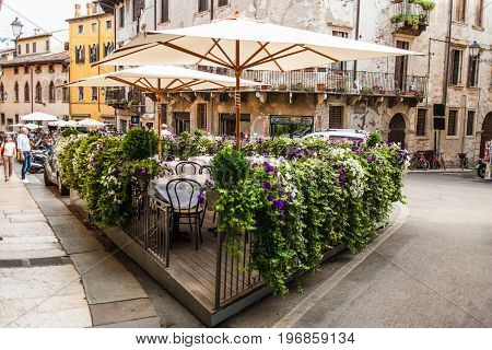 Verona Italy - June 26 2017: Verona Italy - Old Cozy outdoor cafe in Verona Italy Postcard of Verona streets
