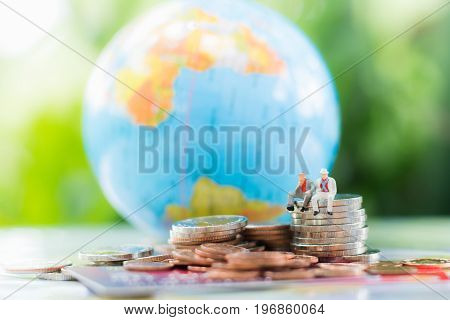 Miniature businessman sitting on the stack of coins with credit card or debit card blurred globe and a pile of coins background using as commitment agreement investment partnership E-commerce and online business concept.