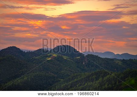 Beautiful dramatic sky sunset in the mountains with orange clouds. In Pang Ma Pha Meahongson Thailand.