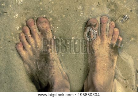 feet under the water standing on sandy bottom and bubbles on water surface above foot on sunny day summer background