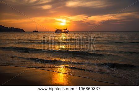 Beautiful sunset on the beach with fishing boat. Phuket Thailand.