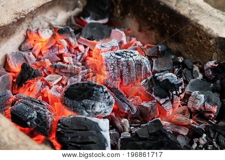 Burning hot coals lie in the fire and smolder
