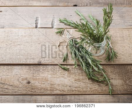 Aromatic twigs of rosemary on the wood table