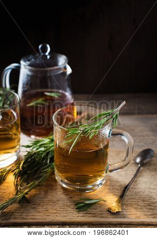 Herbal tea with aromatic rosemary on wood table