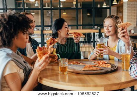 Group of young multiethnic friends having pizza in cafe