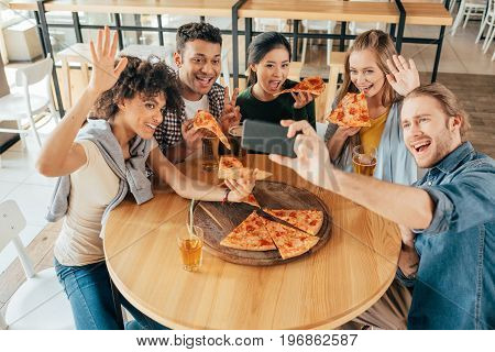 Young Man Taking Selfie With Multiethnic Friends Having Pizza In Cafe