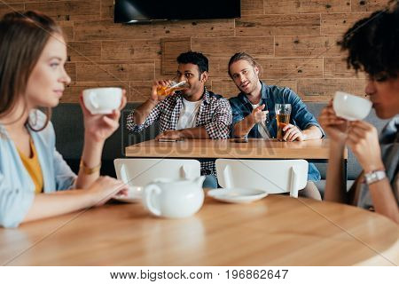Two Young Men Having Beer And Looking At Women Sitting At Next Table In Cafe
