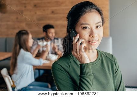 Asian Woman Talking On Smartphone While Her Friends Sitting Behind In Cafe