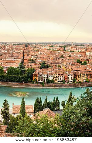 Panoramic view to City of Verona with river at sunny day at sunset. Veneto region Italy. Sunny summer day panorama sky with clouds and famous european italian terracotta color houses bird view