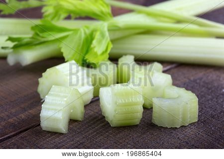 Fresh green celery with slices on wooden table background