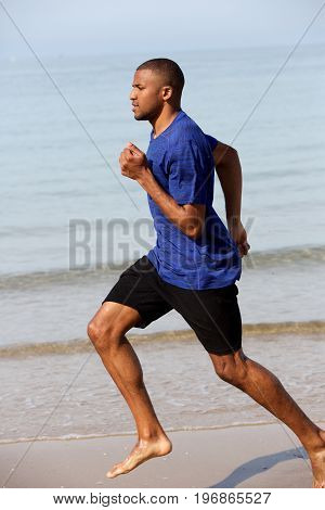 Young African Man Running Along The Beach