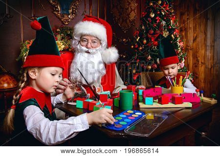 Santa Claus and the elves make gifts for children at Christmas. Workshop of Santa Claus. Christmas concept.