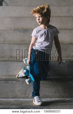 Little boy standing with a skateboard on the stairs