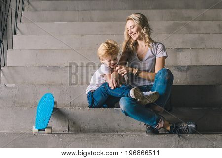 Mother with son sitting on a stairs with skateboard