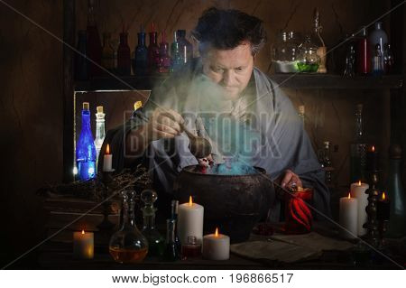 the wizard brews a potion in dark room
