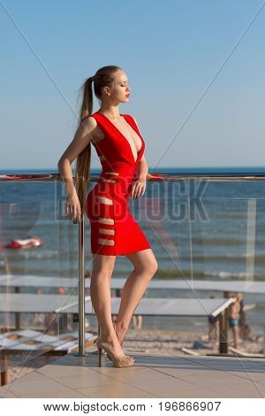A confident sexy lady in a red dress is standing on a transparent balcony on a blue sky background. A pretty lady with a long ponytail is enjoying the sunlight. Luxurious lifestyle.