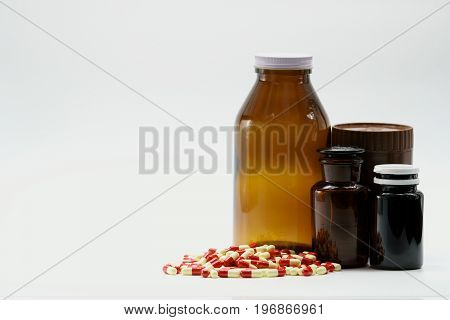 Capsule pills and amber bottles with cap on white background