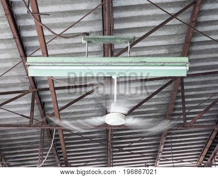 Old ceiling fan is moving near the electric lamp on the metal fram of the canteen