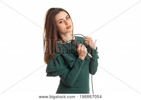 Charming brunette lady in green dress with microphone isolated on white background