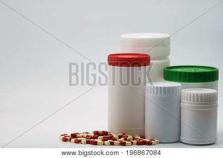 Antibiotic capsules with closed bottles on white background