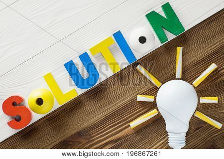 Word Solution from wooden letters on two color wooden boards top view. Concepts of business education and innovation. Word Solution and light bulb on the wooden background flat lay.