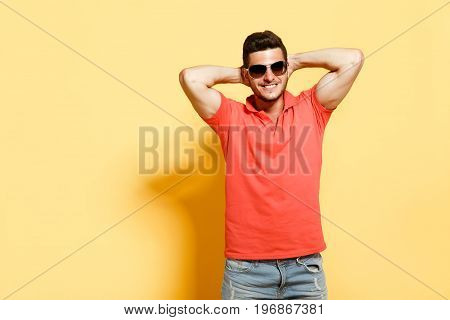 Handsome brunette guy in sunglasses holding hands behind head smiling wearing red shirt standing against yellow background.
