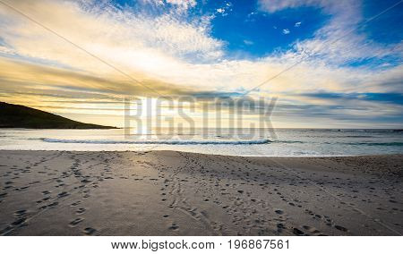 Footsteps Tracks In Sand On Beach With Sunrise Or Sunset.