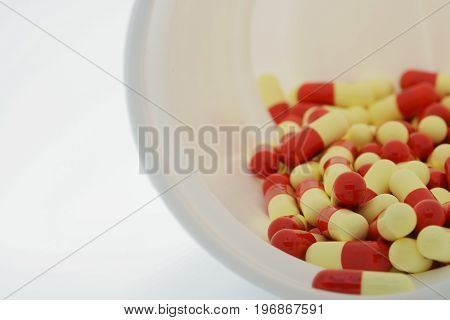 Antibiotic capsules in plastic bottle on white background