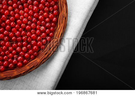 A brown wooden crate on a gray fabric and on a black background. Colourful red currant full of nutritious vitamins. Close-up ripe fresh currant. Delicious berries.