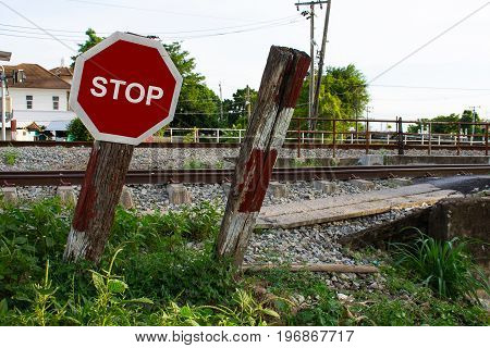 Old fashioned wooden stop sign railway background.Stop sign close-up on a wooden pole