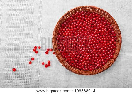 Beautiful nutritious currant in a brown wooden basket on a grey background. Tasteful, ripe red currant in a crate.  A few red berries near the crate. Healthful breakfast for vegetarians.