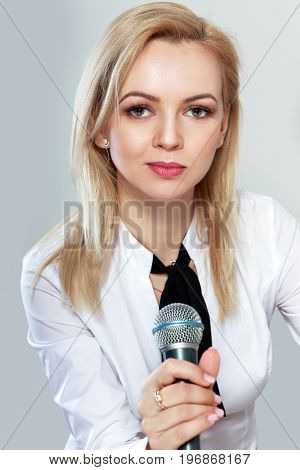 half length portrait of beautiful young woman holding microphone in her hand posing next to color background