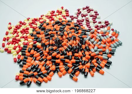 Orange black grey white red pale yellow capsule pills on white background