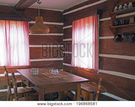 interior of old timbered cattage house with oak table chairs and painted cups with two windows with checked curtains