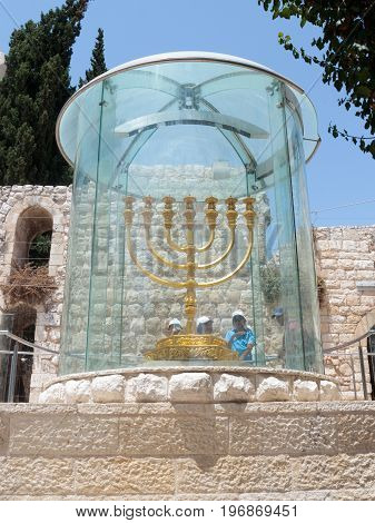 Jerusalem Israel July 14 2017 : Tourists view and photograph Menorah - the golden seven-barrel lamp - the national and religious Jewish emblem near the Dung Gates in the Old City of Jerusalem Israel