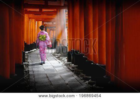 Woman dressed in traditional japanese costume walking under tori gates at the fushimi-inari shrine Kyoto Japan
