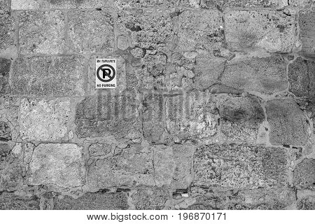 one street sign the parking of motor transport is forbidden on an old stone wall of monochrome tone