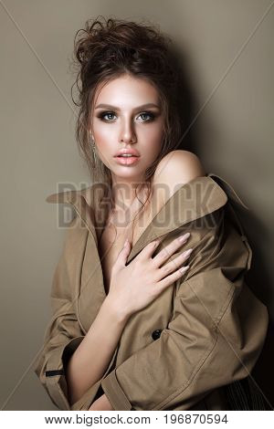 beautiful young woman in trench cout with evening make up and hairdo, perfect skin. Trendy smoky eyes. Sexy look