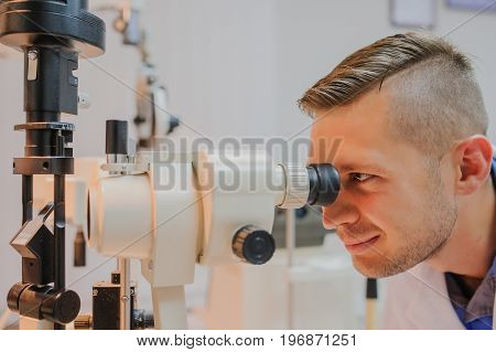 Young beautiful doctor/eye specialist/optometrist in an ophthalmologic clinic test the biomicroscop with slit lamp . poster