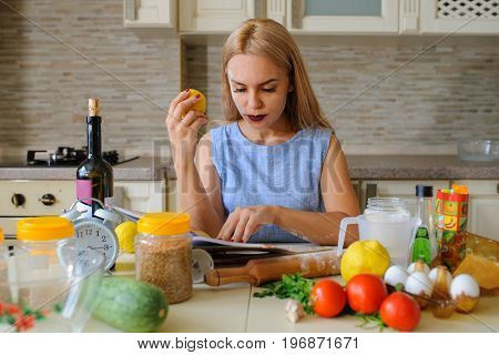 Happy Housewife Reading Cooking Book In Her Kitchen