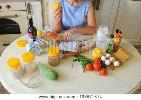Housewife Reading Cooking Book In Her Kitchen Top View
