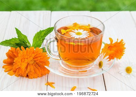 Tea with marigold and chamomile on a light wooden table.