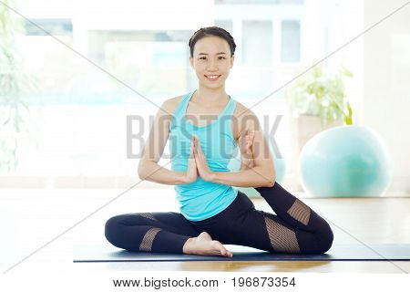 Asian woman training yoga indoor class in pigeon and namaste asana posture with joyful relax and meditate emotion wellness well being and healthy lifestyle concept