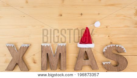 Christmas hat and the letters XMAS on wood, spruce, fir