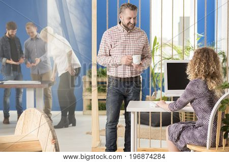 Manager talking to his employee and having a cup of coffee