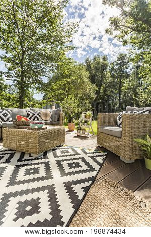 Cosy house veranda with mosaic carpet and comfortable garden armchairs