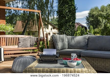 Veranda of a house with garden furniture wooden swing and typewriter on a coffee table