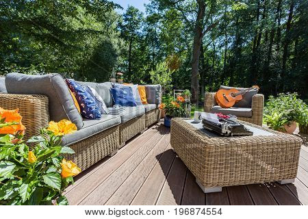 Veranda of a house in a sunny day with the garden wicker furniture